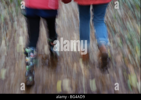 motion blurred image of a mother and her daughter walking in autumn woodland Pembrokeshire Wales UK - Stock Photo