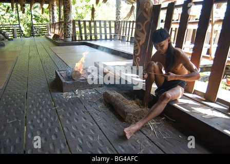 Orang Ulu tribesman whittling wood in longhouse, Sarawak Cultural Village, Kuching, Sarawak, Malaysian Borneo, Malaysia - Stock Photo