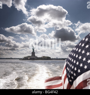 View of Statue of Liberty from rear of bot with Stars and Stripes flag, New York, United States of America, North - Stock Photo