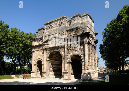 Couple Walk by the Roman Arc de Triomphe or Triumphal Arch (c20BC), Roman Classical Architecture, Orange, Provence, - Stock Photo
