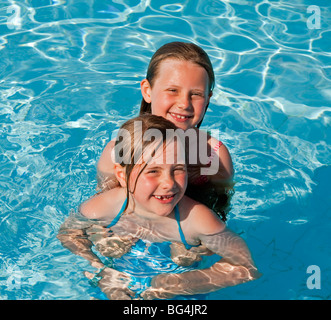 Two young caucasian girls happily playing in a swimming pool - Stock Photo