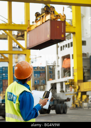 A port worker overseeing a the loading of a ship at a commercial container shipping port. - Stock Photo
