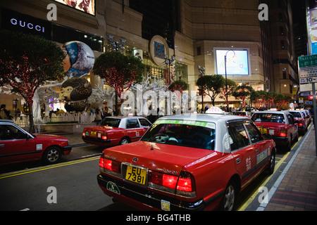 Taxicabs queue up at Times Square shopping mall, Causeway Bay, Hong Kong, China. Christmas season 2008. - Stock Photo