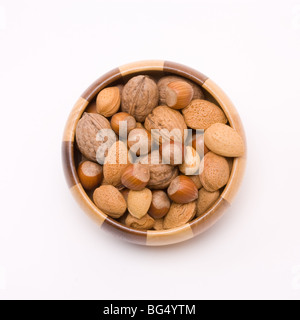 wooden bowl filled with mixed nuts in their shells, hazelnuts, walnuts and almonds. - Stock Photo