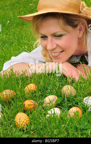 Young woman and easter eggs on the grass - Easter time - Stock Photo