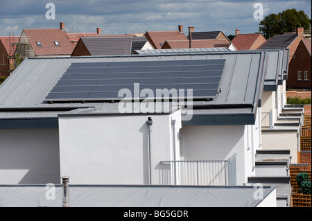 Roof-mounted photo voltaic solar panels on a new housing estate - Stock Photo