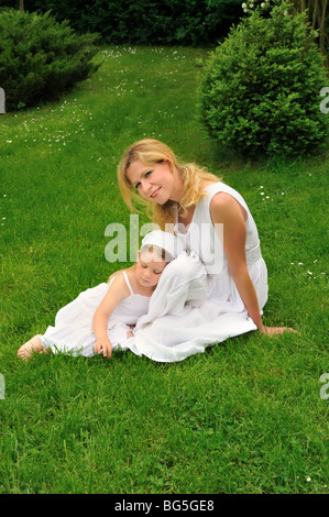 Young mother and daughter resting in meadow - Stock Photo