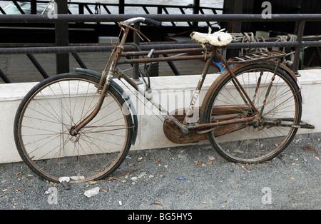 A rusty bicycle leaned on a balustrade, Dubai, United Arab Emirates - Stock Photo