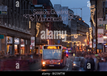 UK, England, Manchester, Cross Street, Metroshuttle free city centre bus under Christmas lights - Stock Photo