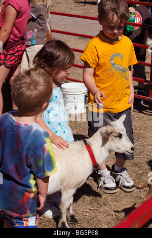 Children with a goat at a petting zoo - Stock Photo