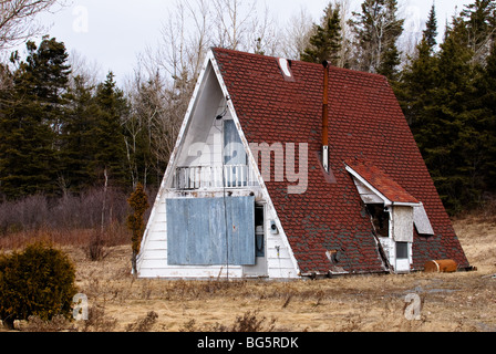 Small abandoned A-frame house. - Stock Photo