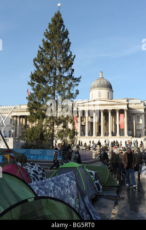 Christmas tree and tents in Trafalgar Square during Climate Change conference in Copenhagen - Stock Photo