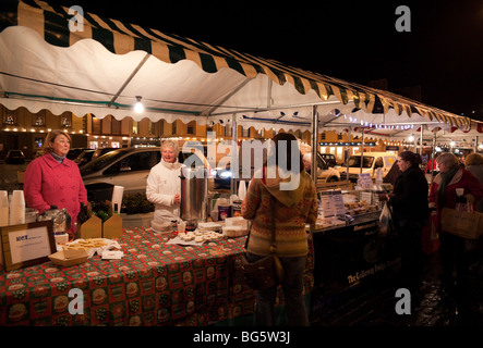 Pre Christmas late shopping in Scottish town of Kelso farmers market with stalls round the tree in the square December - Stock Photo