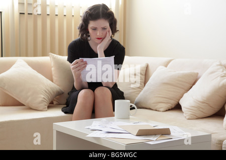 Woman looking stressed reading a bank statement - Stock Photo