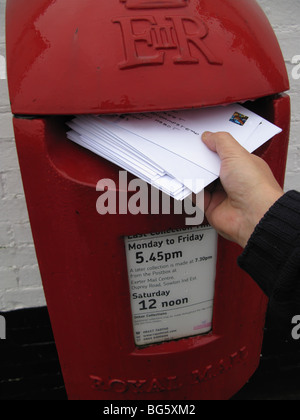 hand posting christmas cards letter in modern design UK post box - Stock Photo
