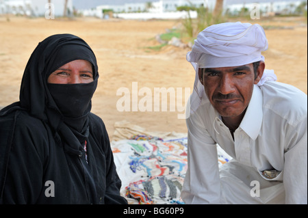 Bedouin couple in traditional dress sitting on beach, Nuweiba, Sinai, Egypt - Stock Photo