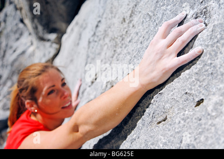 Female climber reaching for hold on rock face, Banff, Banff National Park, Alberta, Canada - Stock Photo