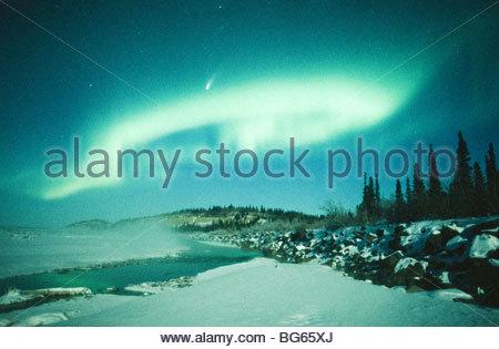 Alaska. Big Delta. The comet Hale-Bopp shines brightly through northern lights over the Delta River. - Stock Photo