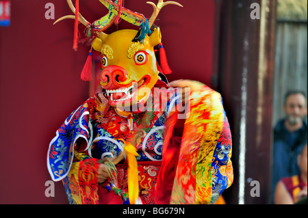 Tibetan Monk in Traditional Dress, Performing Ritual Animal Mask Dance, Buddhist Ceremony, Pagoda - Stock Photo