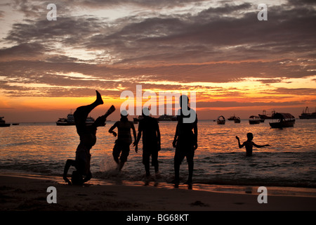 Youths play at sunset along the shores of the Indian Ocean in Stonetown, Zanzibar, Tanzania. - Stock Photo