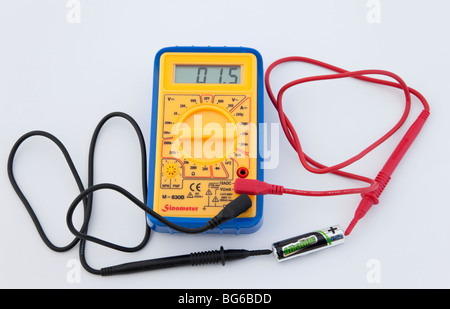Digital multimeter measuring AA battery voltage on a white background. - Stock Photo