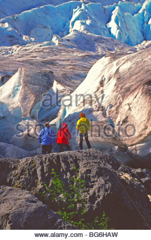 Alaska. Kenai Fjords National Park. Exit Glacier. Tourists stand at the base of the glacier in amazement. - Stock Photo