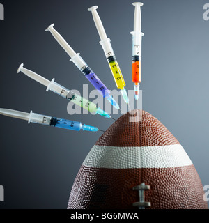 five syringes threaded in american football ball. - Stock Photo