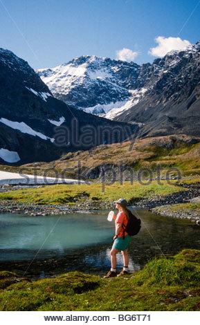 Alaska. Crow Pass. Chugach Mts. Hiker, Thalia Wilkinson enjoys the view of a small glacier lake. MRA - Stock Photo