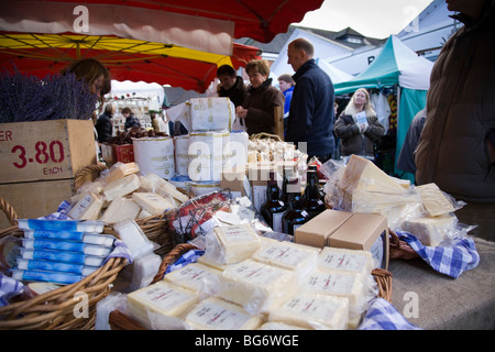 A selection of cheese and other foods on sale from a market stall. - Stock Photo