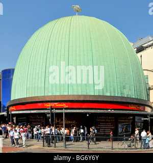 People in London street scene below green patina coating on copper roof of dome at part of Madame Tussauds Wax Museum - Stock Photo