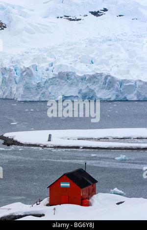 Red hut at Almirante Brown (Argentina) station, Paradise Bay, Antarctica - Stock Photo