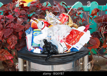 Overflowing litter bin in street in Spain - Stock Photo