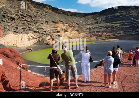 Tourists at viewing point at Lago de los Clicos (green lagoon) near El Golfo on Lanzarote in the Canary islands. - Stock Photo