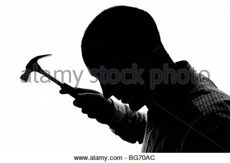 Silhouetted man with hammer - Stock Photo