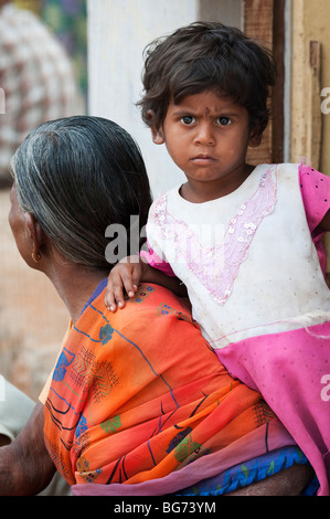 Indian toddler leaning on her grandmother in the doorway of there house in a rural indian village. Andhra Pradesh, - Stock Photo