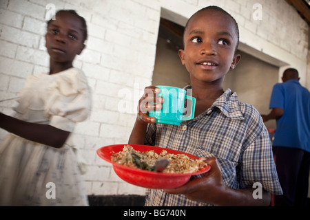 A child receives a meal at a food kitchen in Mererani, Tanzania, the world's only source of Tanzanite. - Stock Photo