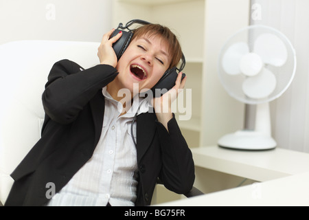 The young woman with ear-phones on a head sings on a workplace - Stock Photo
