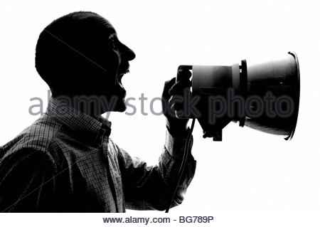 Silhouetted man with loudhailer - Stock Photo