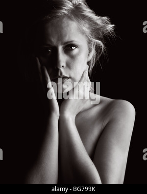 Low Key Shot of a Vulnerable Blonde Woman - Stock Photo