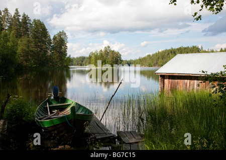 Old Finnish boathouse  , made of logs ,  and a wooden rowboat at lake Konnevesi shore , Finland - Stock Photo
