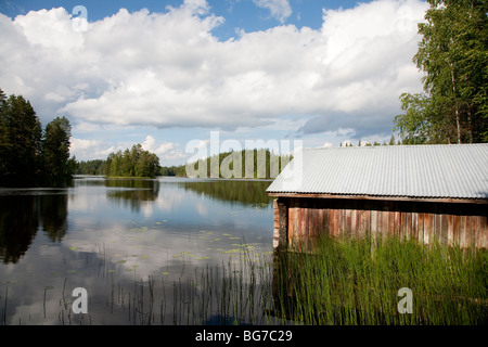 Old Finnish boathouse , made of logs , at lake Konnevesi shore , Finland - Stock Photo