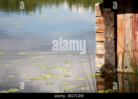 Corner of an old Finnish wooden boathouse , made of logs , in water - Stock Photo
