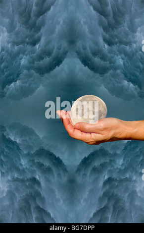 This image was put together by shooting the hand, the clouds during a storm and the moon while nearly full. - Stock Photo