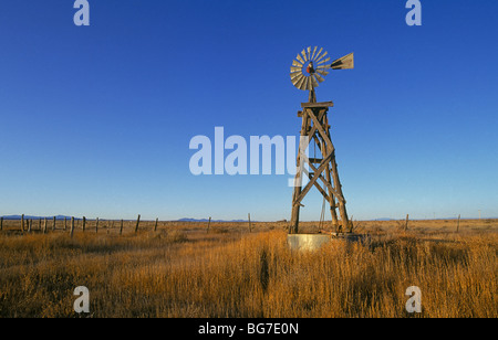 An old wooden water pumping windmill in a field of weeds on an abandoned bean farm in central New Mexico - Stock Photo
