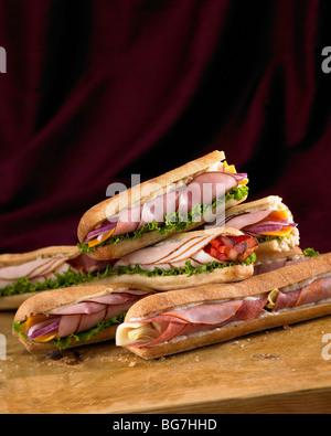Assorted deli sandwiches on a cutting board - Stock Photo