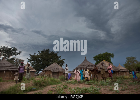 Residents stand outside their mud houses in Acowa refugee camp in Amuria District, Uganda, East Africa. - Stock Photo