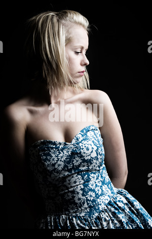 Low Key Shot of a Pretty Blonde Girl in Blue Floral Dress - Stock Photo