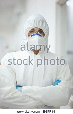 Scientist in protective clothing with arms crossed - Stock Photo