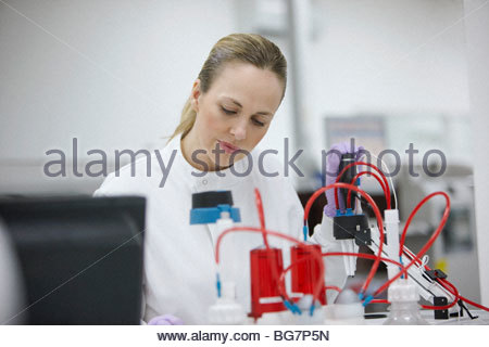 Scientist working with equipment in laboratory - Stock Photo