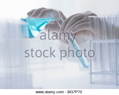 Scientist pouring liquid from beaker into test tube - Stock Photo